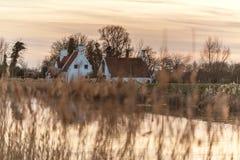White Farm House Near Canal at Sunrise Stock Photography