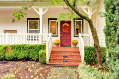 White farm house with red door during fall. Stock Photos