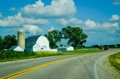 White Farm with Silo on a Curvy Country Road. A white barn with a silo on a curvy S country road in Wisconsin in Kenosha County royalty free stock photo