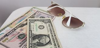 White fashionable sunglasses lay near american dollars paper bills stock images