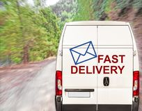 White FAST DELIVERY Van driving fast on forest road. Close Royalty Free Stock Images