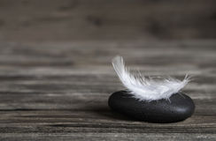 White feather on a black stone: idea for a condolence card. White feather on a black stone: idea for a condolence card or balance conecpt Royalty Free Stock Images