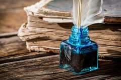 White feather on blue inkwell and old book Royalty Free Stock Images
