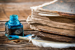 White feather on blue inkwell and old book. On old wooden table Royalty Free Stock Image