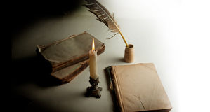 White feather in the inkwell, burning candle and couple of an ol Stock Image