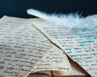 White feather on old documents. Close up photo.Natural light Royalty Free Stock Images