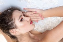 White feather soft feelings. Fashion girl makeup face relax feather bed. Skin care. Pure beauty. Pretty girl naked body. With feather in hair. Cute girl royalty free stock images