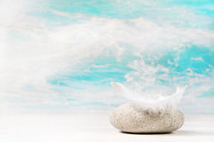 White feather on a stone: background for a condolence or spa con Stock Photo