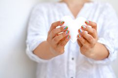 White felted heart in femaile hands with rainbow manicure. Love, valentine, lgbt, pride concept Royalty Free Stock Image