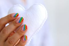White felted heart in femaile hands with rainbow manicure. Love, valentine, lgbt, pride concept Royalty Free Stock Photo