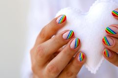 White felted heart in femaile hands with rainbow manicure. Love, valentine, lgbt, pride concept Stock Images