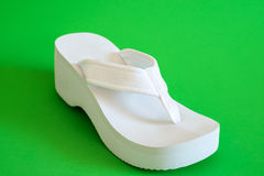 White female beach shoes on green background. White female beach shoes on a green background Royalty Free Stock Photography