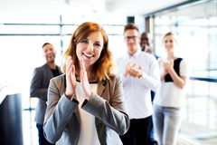 White female executive standing in front of colleagues clapping Royalty Free Stock Photography