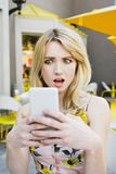 White Female Girl Looks at Her Smart Phone in Deep Shock Outdoors stock image