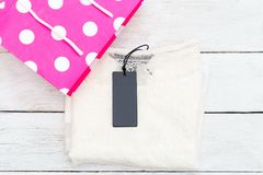 White female shirt with a label in a pink shopping bag. Flat lay Royalty Free Stock Photography