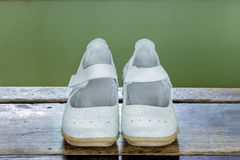 White female shoes on grunge wooden with green background. Stock Photography