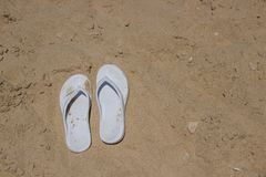 White slippers on golden sand. White female slippers lie on the sand by the sea stock photography