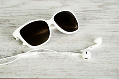 White female sunglasses and headphones on a light wooden backgr. Ound horizontal royalty free stock image