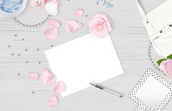White feminine background. Flat lay. Pink roses, mirror, leaves, gift, bag. Stock Photos
