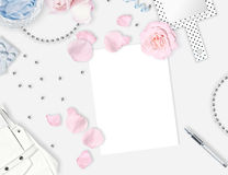 White feminine background. Flat lay. Pink roses, mirror, leaves, gift, bag. Stock Photography