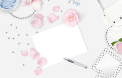 White feminine background. Flat lay. Pink roses, mirror, leaves, gift, bag. Royalty Free Stock Photo