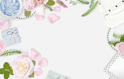 White feminine background. Flat lay. Pink roses, petals, mirror, green leaves, gift, bag. Place for text. Cheerful mind every stock photos