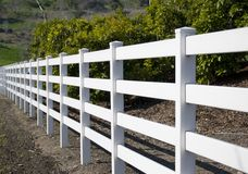 White fence. A white wooden fence in an avocado field Royalty Free Stock Photo