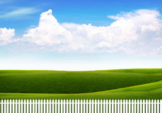 White fence against a bright sky with clouds Stock Photography