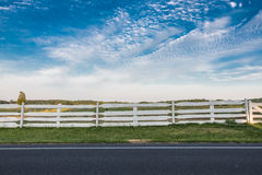 White Fence along the Side of a Road. With Cloudy Blue Sky Stock Image