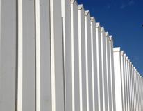 White fence on a background of blue sky. White plastic fence on a background of blue sky Royalty Free Stock Image