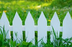 White fence on a background of green grass stock photography
