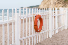 White fence on beach with a life buoy Stock Photo