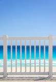 White fence and blue ocean on a tropical beach Stock Photos