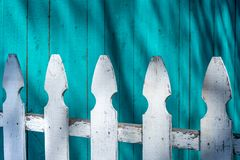 White fence on bright blue wooden planks painted wall background. White weathered wooden fence on a bright blue painted textured wooden wall with vertical planks royalty free stock photography