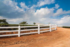 White fence beside country road. With cloudy sky stock images