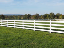 White fence by a field Stock Photo