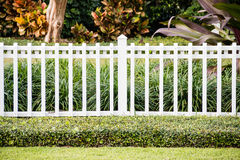A white fence in front of a representative home Royalty Free Stock Image