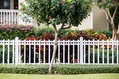 A white fence in front of a representative home. A white fence in front of a cozy and representative home with a very well-groomed green lawn Stock Photos