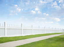 White fence, grass, sidewalk, blue sky and clouds
