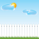 White fence and green grass on blue sky background Royalty Free Stock Photography