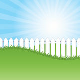 White fence and green grass on blue sky background Royalty Free Stock Photo