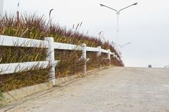 White fence on green hill side. Royalty Free Stock Photo