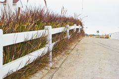 White fence on green hill side. Royalty Free Stock Photography