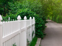 White fence and green street Royalty Free Stock Image