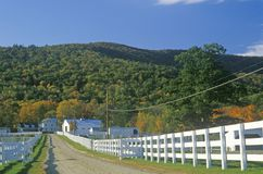 A white fence leading to a home in New Hampshire Royalty Free Stock Photography