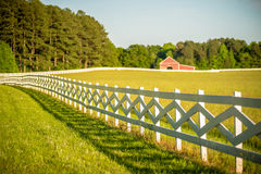White fence leading up to a big red barn Royalty Free Stock Images