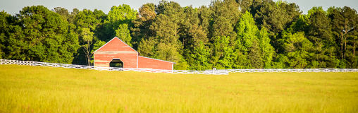 White fence leading up to a big red barn Stock Images