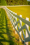 White fence leading up to a big red barn Stock Image