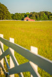 White fence leading up to a big red barn Royalty Free Stock Image