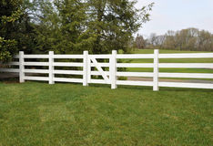 White fence by a meadow Stock Photo